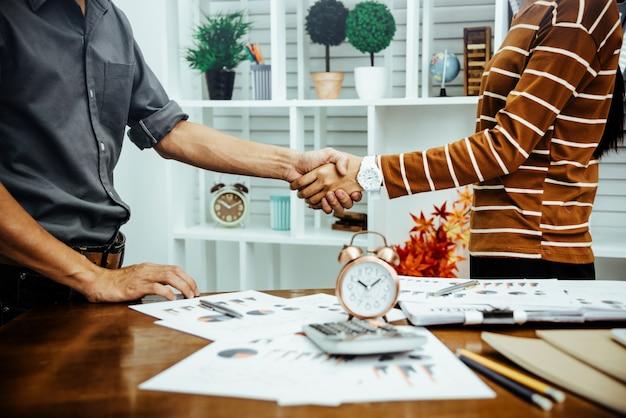 A mulher e o homem de negócios agitam as mãos cumprimentam ou agradecem o gesto do conceito do negócio.