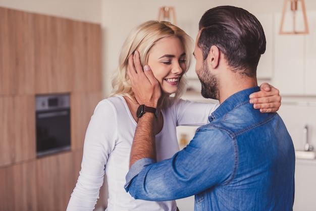 A mulher e o homem novo bonito estão abraçando e estão sorrindo.