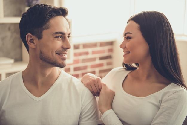 A mulher e o homem novo bonito estão olhando se.