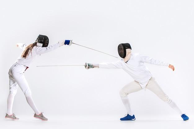 A mulher e o homem vestindo terno de esgrima praticando com espada contra cinza