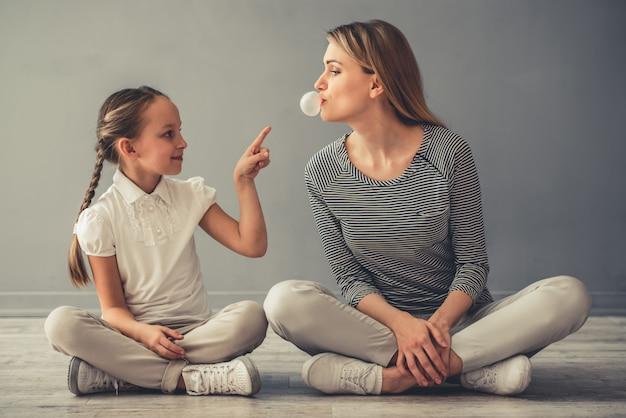 A mulher e sua filha bonito estão jogando com goma de mastigação.