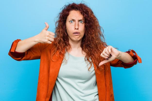 A mulher elegante do ruivo novo que mostra os polegares acima e os polegares para baixo, difícil escolhe o conceito