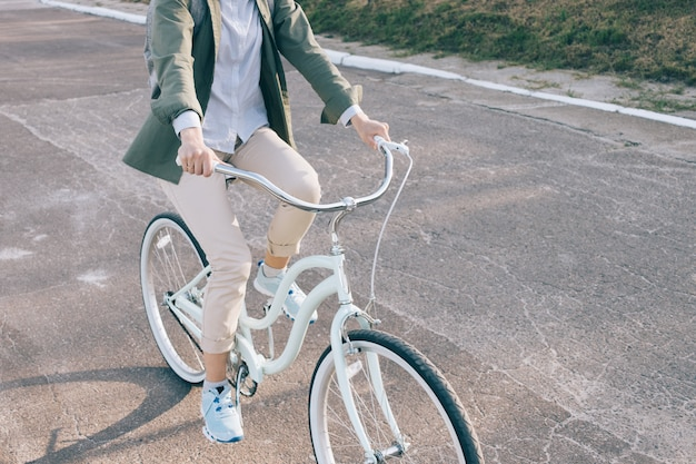 A mulher elegante em uma camisa verde monta na bicicleta da cidade na estrada