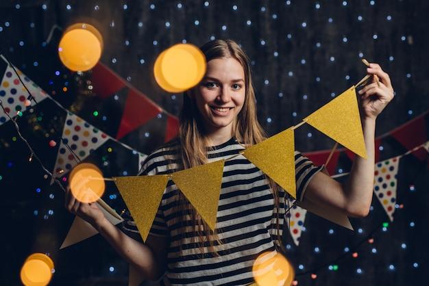 A mulher em casa que pendura bandeiras do partido das luzes de natal decora artigos para a celebração do ano novo