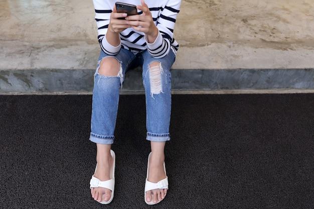 A mulher em jeans rasgados olha para o telefone móvel.