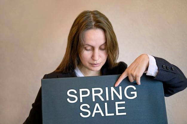 A mulher em liquidação de primavera se levanta e aponta o dedo para a inscrição venda de primavera no quadro negro