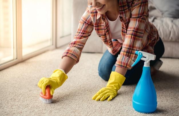 A mulher em luvas protetoras está sorrindo, limpando usando um detergente.