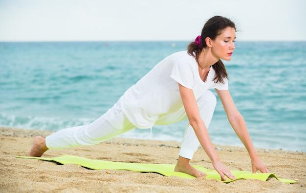 A mulher em t-shirt branco está praticando alongamento