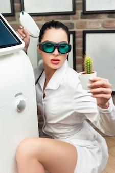 A mulher em um estúdio de depilação a laser posa com um cacto