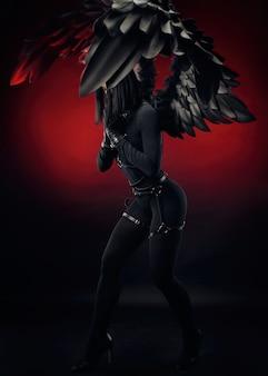 A mulher em um macacão preto com alças de couro e asas pretas sobre um fundo vermelho escuro