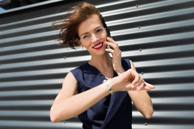 A mulher em um terno de escritório marcou uma consulta e ligue para o telefone