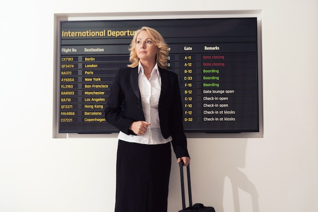 A mulher em um terno está estando no aeroporto.