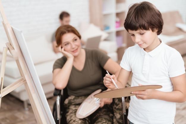 A mulher em uma cadeira de rodas olha suas pinturas do filho na lona.