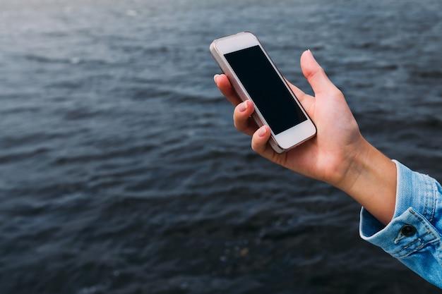 A mulher em uma jaqueta jeans segura o celular na mão