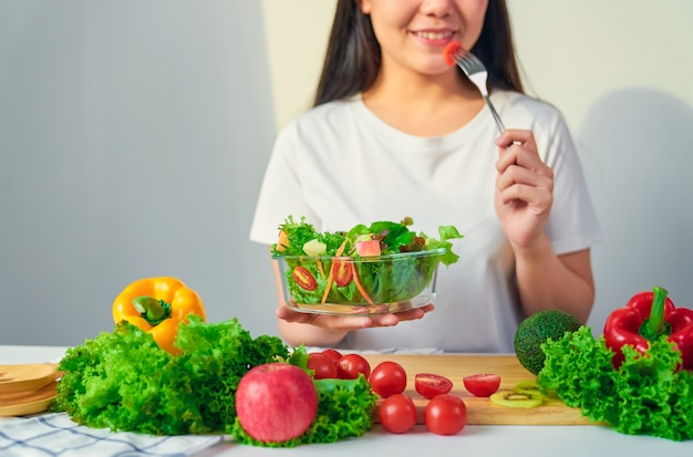 A mulher entrega guardar a bacia de salada com comer o tomate e os vários vegetais folhosos verdes na tabela em casa.