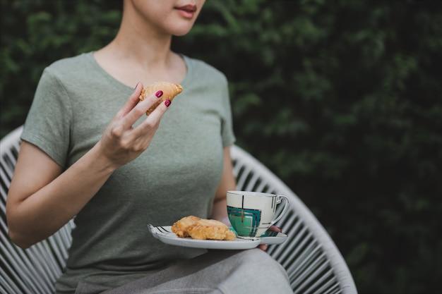 A mulher entrega guardar o petisco com a xícara de café que senta-se no jardim em casa.