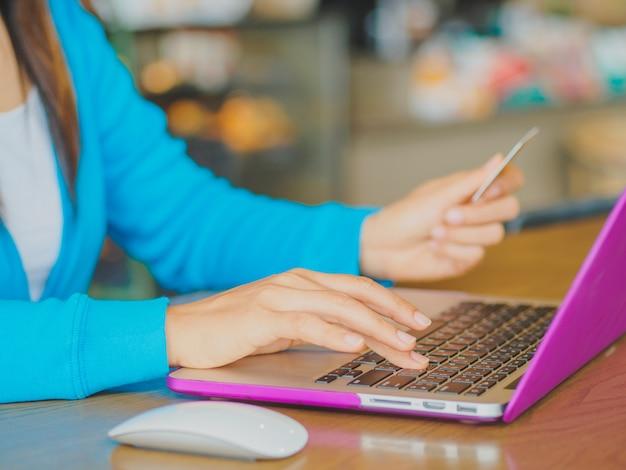 A mulher entrega guardar um cartão e um laptop de crédito para a compra em linha.
