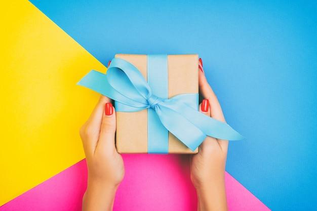 A mulher entrega manter o presente envolvido e decorado com curva azul em azul, em rosa e em amarelo com copyspace. toned