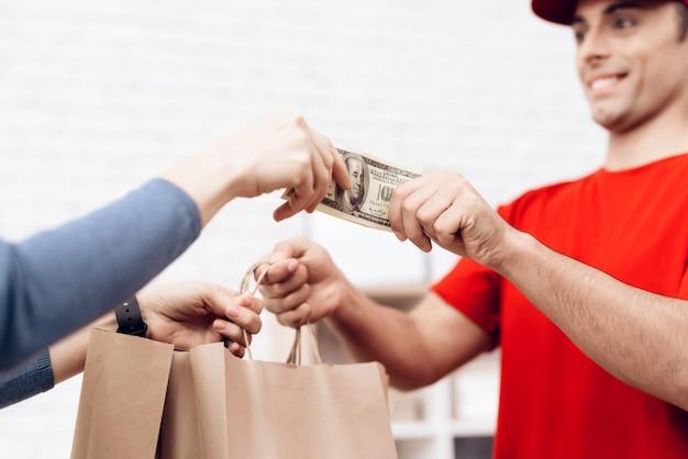 A mulher entrega o dinheiro para o homem de entrega da pizza.