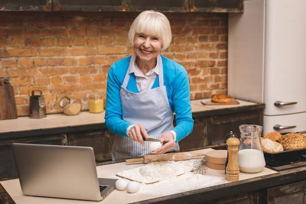 A mulher envelhecida sênior atrativa está cozinhando na cozinha. avó fazendo cozimento saboroso. usando laptop