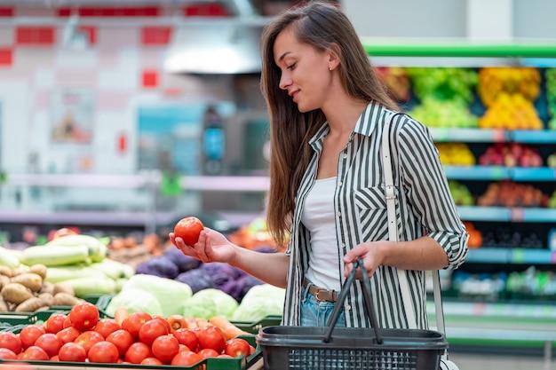 A mulher escolhe tomates maduros frescos no departamento vegetal do supermercado. cliente que compra comida na mercearia