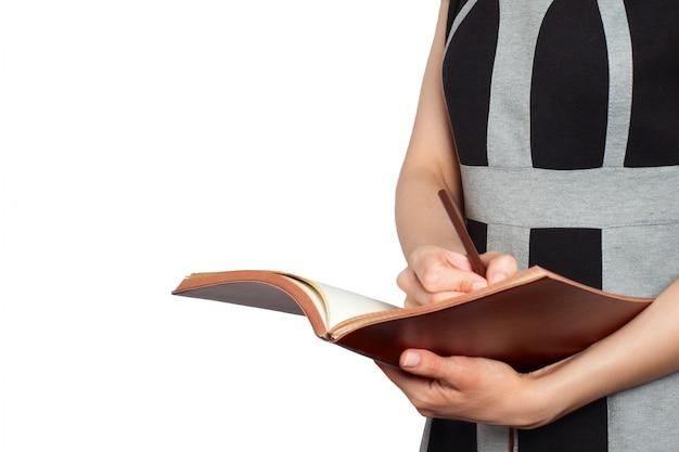 A mulher escreve com a pena marrom no caderno marrom no fundo branco.