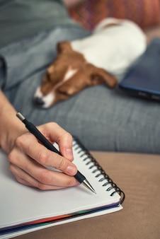 A mulher escreve planos no caderno com seu cachorrinho do jack rusel terrier. bons relacionamentos e amizade entre dono e animal de estimação