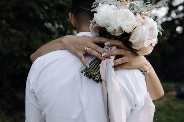 A mulher está abraçando o homem e segurando o buquê de peônias brancas ao ar livre, vista frontal dos detalhes