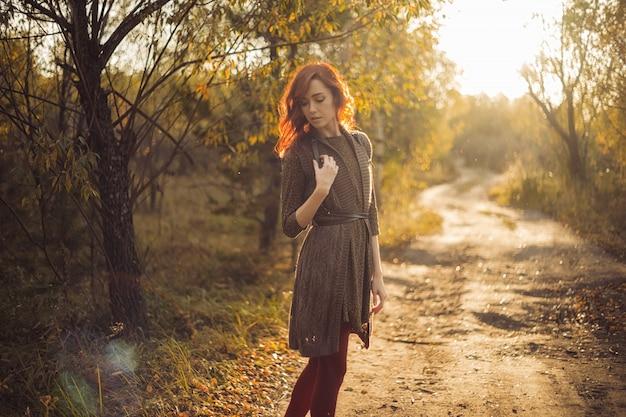 A mulher está andando no parque ao pôr do sol