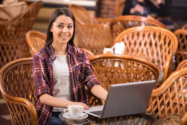 A mulher está bebendo o café e está usando o portátil em uma cafetaria.
