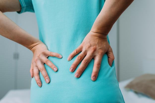 A mulher está com dor lombar devido a dores nos rins.