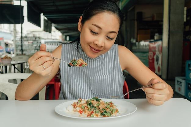 A mulher está comendo o arroz tailandês stir-fried a carne de porco e a manjericão.