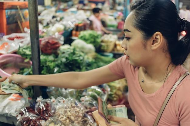 A mulher está comprando no mercado fresco local tailandês.