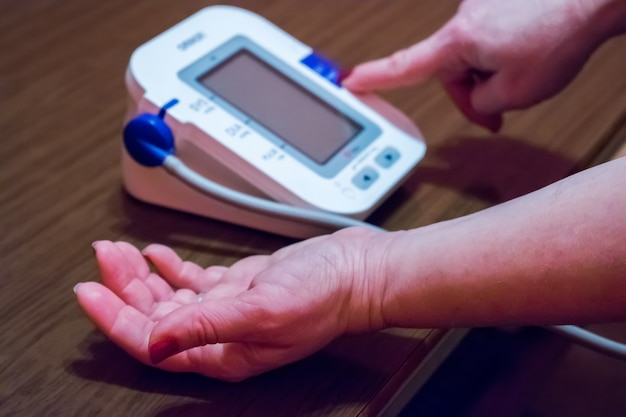 A mulher está cuidando a saúde com monitor de batida e pressão sanguínea