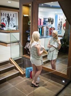 A mulher está de pé na frente do espelho sorrindo