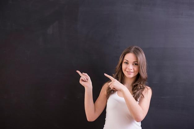 A mulher está de pé na frente do quadro-negro e aponta nele.