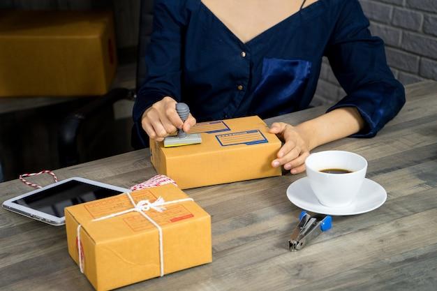 A mulher está empacotando o endereço da caixa e do selo para enviar ao cliente que compra em linha