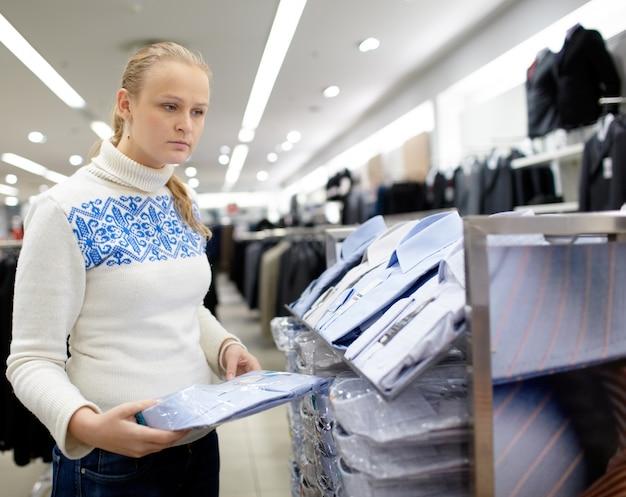 A mulher está escolhendo a camisa para o homem