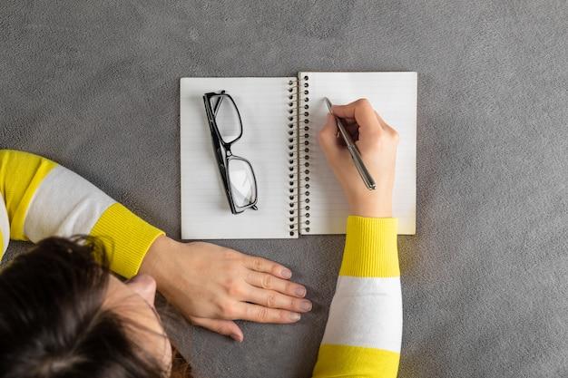 A mulher está escrevendo no caderno de papel