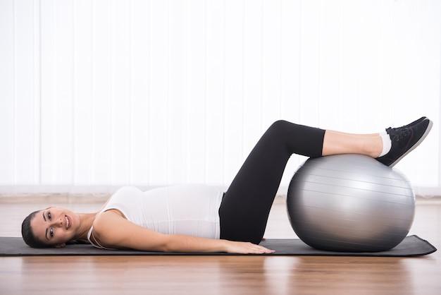 A mulher está fazendo exercícios com bola de ginástica.