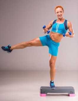 A mulher está fazendo exercícios com halteres na placa da etapa.