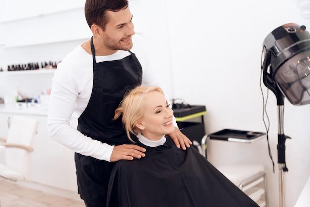 A mulher está fazendo o penteado no salão de beleza.