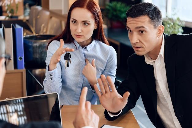 A mulher está guardando nas chaves do dedo que sentam-se ao lado do homem adulto.
