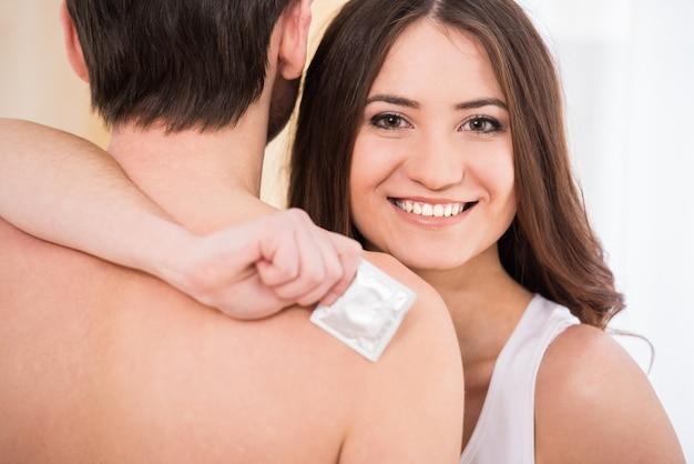 A mulher está guardando um preservativo e sorri.