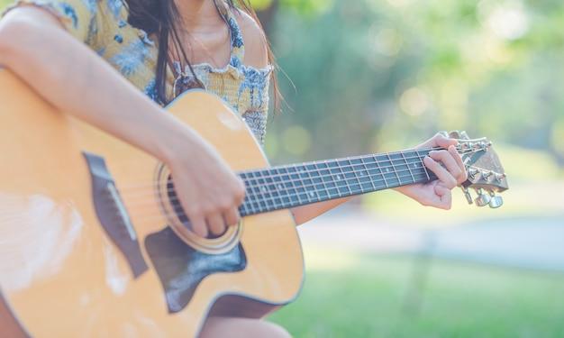 A mulher está jogando a guitarra acústica no jardim.