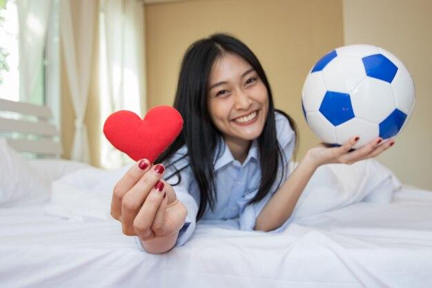 A mulher está jogando com uma bola de futebol no quarto.