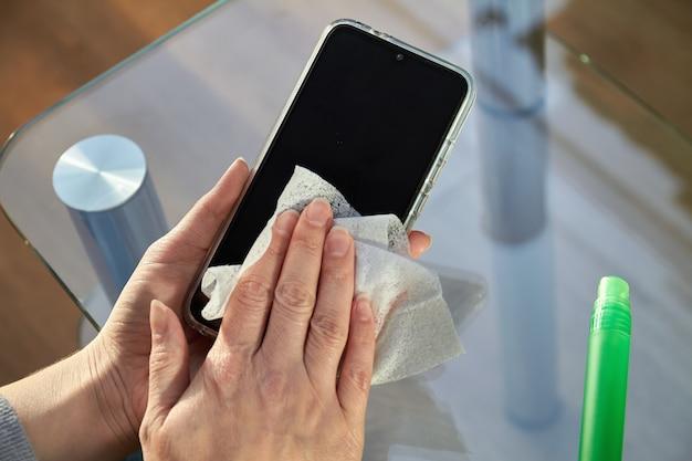 A mulher está limpando um smartphone com um jato de desinfetante para as mãos com álcool aerossol e pano descartável em casa. precauções contra vírus