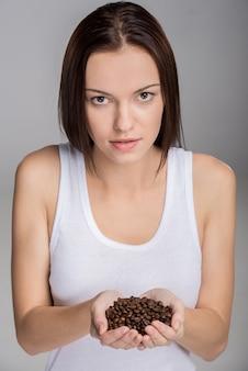 A mulher está mostrando punhado roasted dos feijões de café.