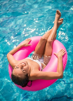 A mulher está relaxando na piscina com anel de borracha.