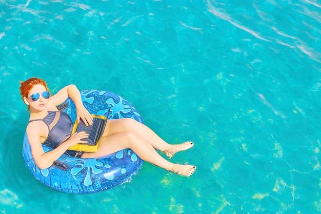 A mulher está relaxando no mar no anel inflável com portátil.